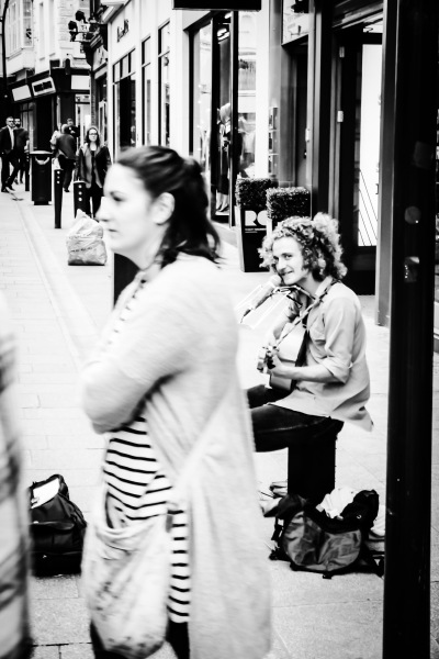 Busker on Grafton Street stares over and smiles as he gets his photo taken