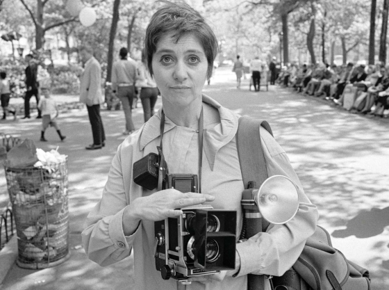 Diane Arbus standing in a park holding cameras