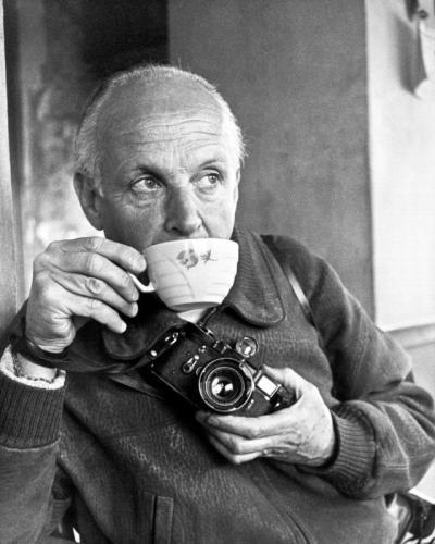 Henri Cartier Bresson takes a sip of tea while holding his camera