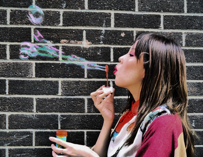 Photograph of woman blowing bubbles as an example of good Photographic exposure