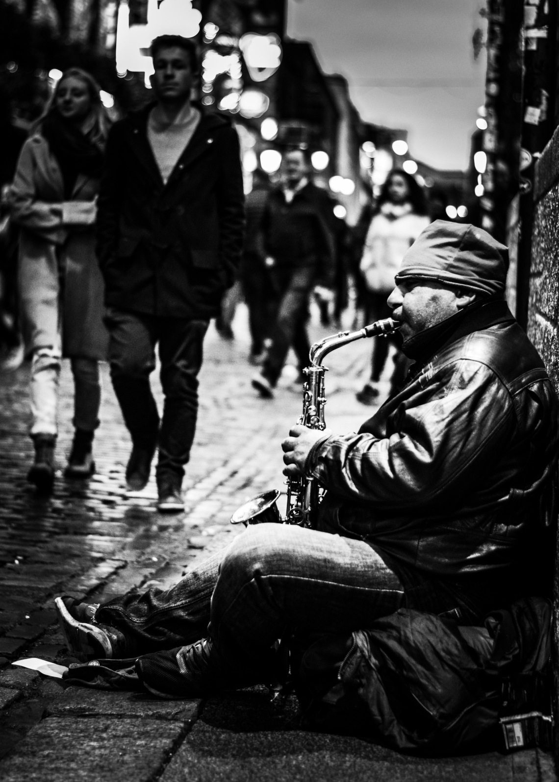 A man plays Jazz on the street to a crowd walking on by