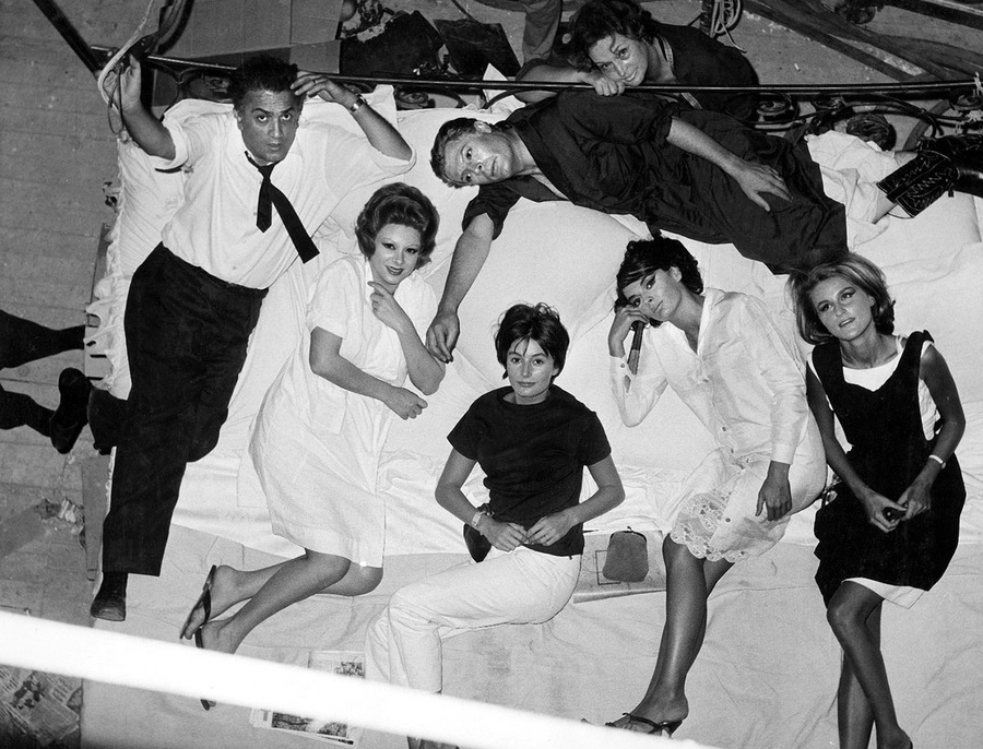 Fellini and his cast all stare at a camera above a bed they are all lying in on the set of 8 1/2