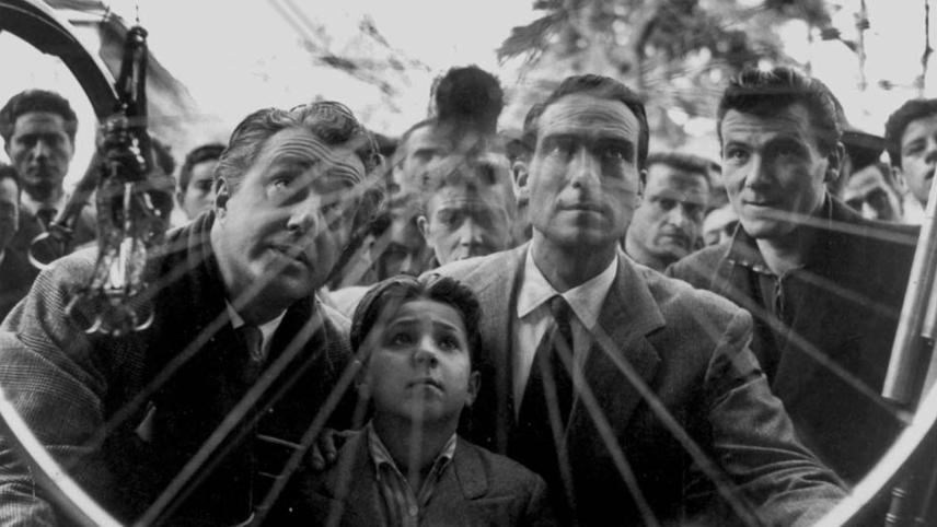 A group of people stare at a wheel of a bicycle in a window in the film Bicycle Thieves