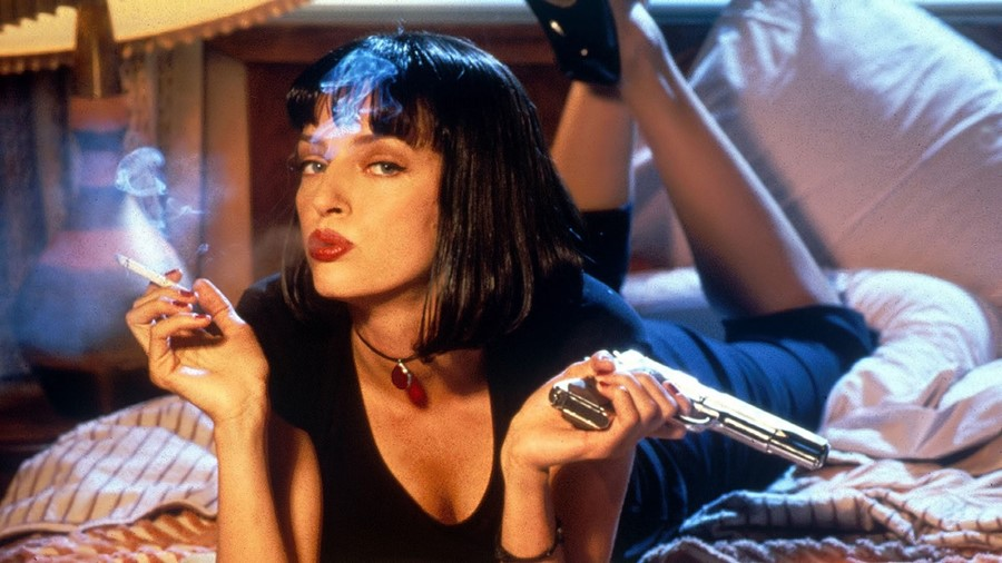 A scene from the movie Pulp Fiction where lady lies on bed with a ciggarette and gun