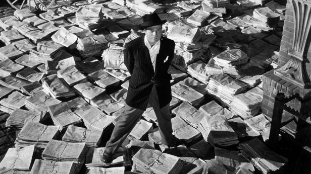 Orson Wells stands on newspapers in the Film Citizen Kane