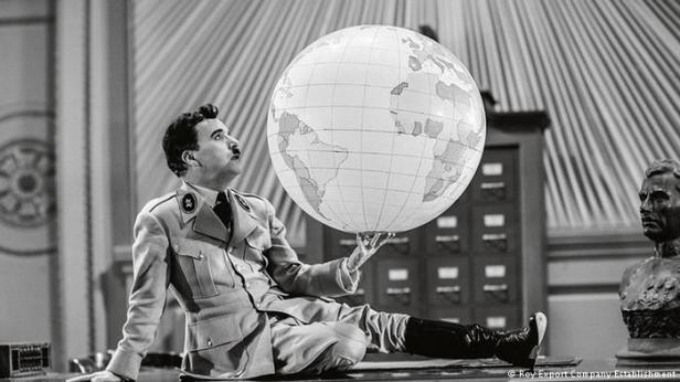 Charlie Chaplin sits on a table with the world in his hands in the film The Great Dictator