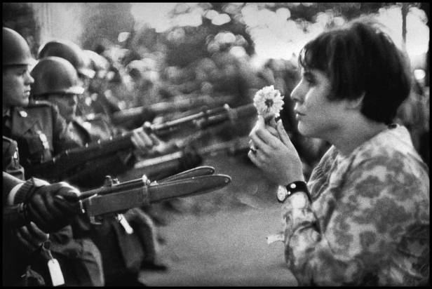 Jan Rose Kasmir offers a flower to a solider at Anti War protest in Washington DC