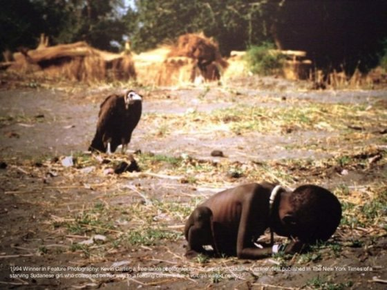 A young girl crawls to the feeding centre in Sudan, starving in need of food as freelance photojournalist takes a photo